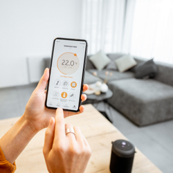 frau bedient smart-home-thermostat ueber handy